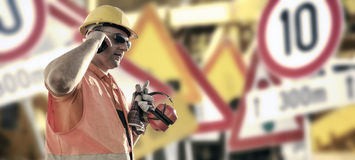 Worker in protective uniform in front of road signs. Worker in protective uniform and protective helmet in front of road signs - toned image, retro film filtered Royalty Free Stock Image