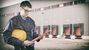 Worker with protective uniform in front of shipping warehouse ga Stock Photos