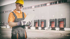 Worker with protective uniform in front of shipping warehouse ga Royalty Free Stock Image