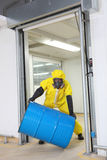 Worker in protective uniform rolling barrel. Worker in protective uniform,mask,gloves and boots rolling barrel of chemicals Royalty Free Stock Images