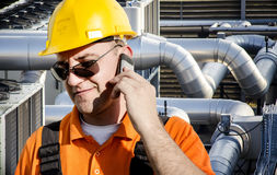 Worker in protective uniform and smart phone Royalty Free Stock Photo
