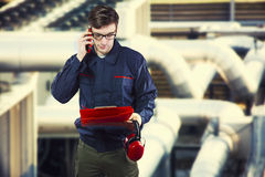 Worker in protective uniform with smartphone Stock Photo