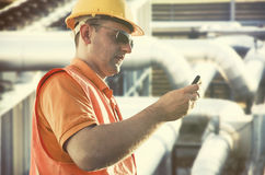 Worker in protective uniform with smartphone Royalty Free Stock Images