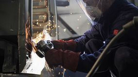 Worker in protective workwear grinds metal truck cabin