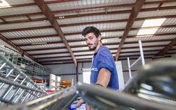 Worker pulling cart in warehouse stock photo