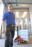Worker pulling inventory on hand truck on loading dock Stock Photos