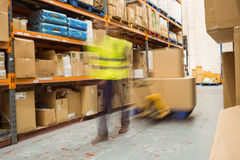 Worker pulling trolley with boxes in a blur Stock Images