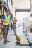 Worker pulling trolley with boxes Stock Photography