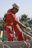 Worker Pulls Hose - Vertical Stock Image