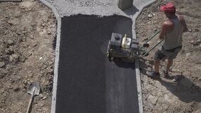 Worker pushes a manual roller for asphalt paving of the sidewalk. Road works close-up,view frome above