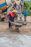 Worker pushing barrow with wet cement to pouring concrete floor Stock Images