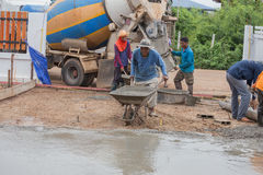 Worker pushing barrow with wet cement to pouring concrete floor Royalty Free Stock Photos