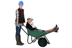 Worker pushing boss in wheelbarrow Royalty Free Stock Photos