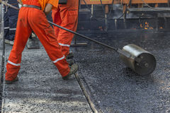 Worker pushing hand roller for mastic asphalt paving Stock Photos