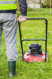Worker pushing lawnmower in garden Royalty Free Stock Photography
