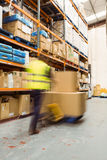 Worker pushing trolley with boxes in a blur Royalty Free Stock Photo