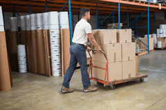 Worker pushing trolley with boxes Stock Image