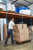 Worker pushing trolley with boxes Royalty Free Stock Photography