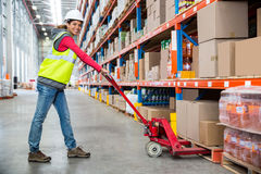 Worker pushing trolley with boxes. In warehouse Stock Photography