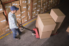 Worker pushing trolley with boxes in warehouse Royalty Free Stock Photo