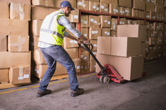 Worker pushing trolley with boxes in warehouse. Side view of worker pushing trolley with boxes in warehouse Stock Photos