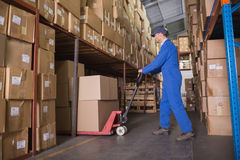 Worker pushing trolley with boxes in warehouse Stock Images
