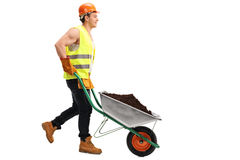 Worker pushing a wheelbarrow with dirt Royalty Free Stock Photography