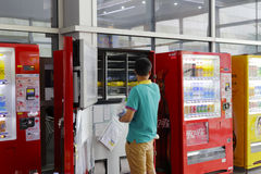 Worker put drinks in the vending machine stock image