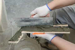 Worker puts the adhesive on the tile. Stock Photo
