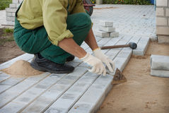 Worker puts the blocks on the sidewalk Royalty Free Stock Images