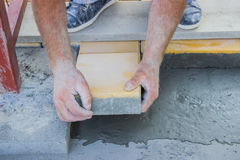 Worker puts concrete pavers Stock Images