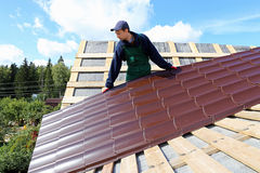 Worker puts the metal tiles on the roof Stock Images