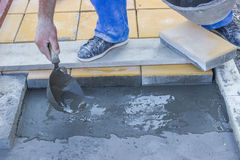 Worker puts mortal for concrete pavers Stock Photography