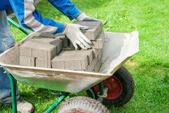 Worker puts paving stabs tile in a wheelbarrow Royalty Free Stock Photos