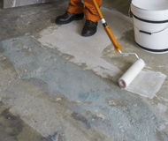 Worker puts primer with roller on concrete floor. Apartment unde Royalty Free Stock Photo