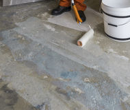 Worker puts primer with roller on concrete floor. Room of house Stock Image
