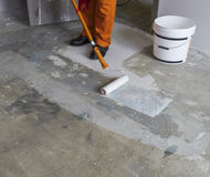 Worker puts primer with roller on concrete floor in room from un Royalty Free Stock Images