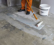 Worker puts primer with roller on concrete floor in room of unfi Stock Photos