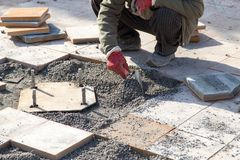 Worker puts sidewalk tile Royalty Free Stock Photography