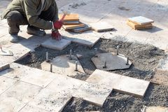 Worker puts sidewalk tile Royalty Free Stock Photos