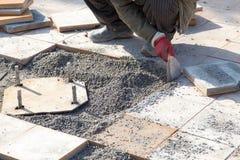 Worker puts sidewalk tile Royalty Free Stock Photo