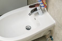 Worker puts silicone sealant. Worker puts silicone sealant to caulk the joint between bidet and wall Stock Images