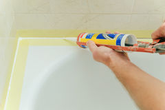Worker puts silicone sealant. Worker puts silicone sealant to caulk the joint between tub and wall Stock Image