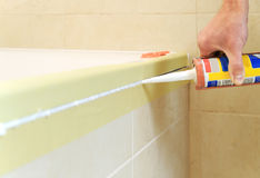 Worker puts silicone sealant. Worker puts silicone sealant to caulk the joint between tub and wall Stock Photography