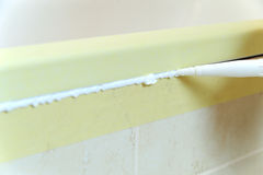 Worker puts silicone sealant. Worker puts silicone sealant to caulk the joint between tub and wall Royalty Free Stock Images