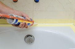 Worker puts silicone sealant. Worker puts silicone sealant to caulk the joint between tub and wall Royalty Free Stock Image