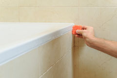 Worker puts silicone sealant. Worker puts silicone sealant to caulk the joint between tub and wall Stock Photos