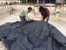 Worker Puts The Tarpaulin Sheet at Roof Royalty Free Stock Photography