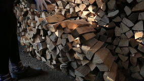 Worker puts wood closeup. Worker with gloves adds firewood stock footage