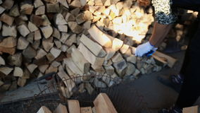 Worker puts wood closeup. Worker with gloves adds firewood stock video